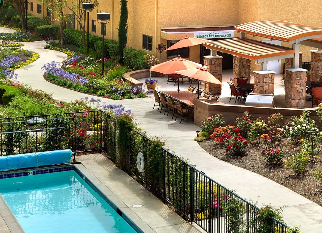The Canterbury exterior is sprinkled with patio chairs and umbrellas. There also is a pool, surrounded by colorful flowers.